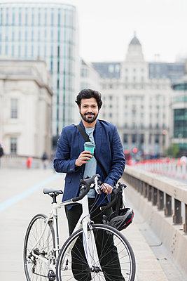 Portrait smiling businessman with coffee and bicycle on city bridge - p1023m2208415 by Paul Bradbury