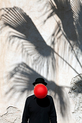 Morocco, Essaouira, man wearing a bowler hat with red balloon in front of his face at a wall - p300m2104314 by Petra Stockhausen