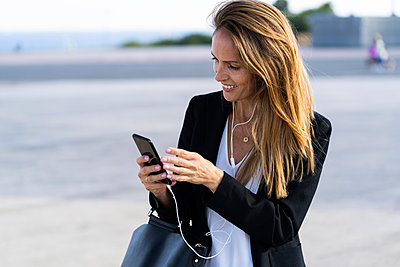 Smiling businesswoman with smartphone and earphones outdoors - p300m2139970 by Giorgio Fochesato