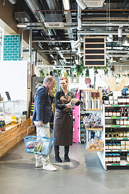Female owner explaining product to mature man in organic supermarket - p426m1407375 by Kentaroo Tryman