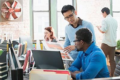 Businessmen discussing design in office - p555m1219569 by Jose Luis Pelaez Inc