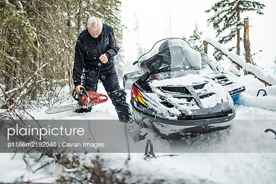 Retired man using chainsaw to clear trails while snowmobiling. - p1166m2192040 by Cavan Images
