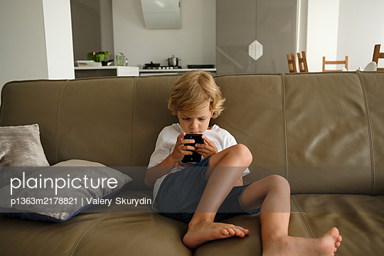 Boy is playing with smartphone at home, stay at home due to Covid-19 - p1363m2178821 by Valery Skurydin