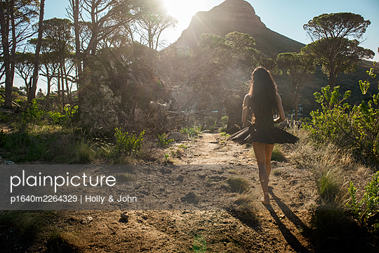 Woman in ballet skirt goes for a walk in the countryside - p1640m2264329 by Holly & John