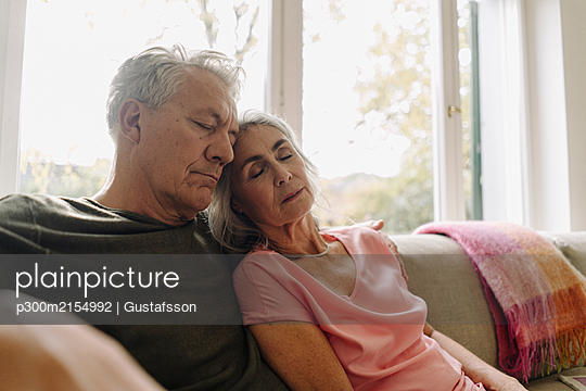 Senior couple napping on couch at home - p300m2154992 by Gustafsson