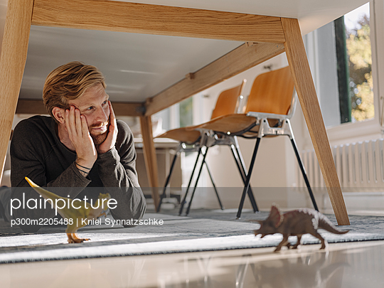 Man with toy dinosaurs under a table at home - p300m2205488 by Kniel Synnatzschke