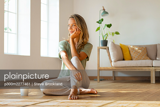 Thoughtful woman with hand on chin sitting on hardwood floor at home - p300m2277461 by Steve Brookland