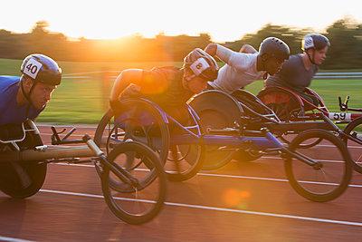 Paraplegic athletes speeding along sports track in wheelchair race - p1023m2067547 by Martin Barraud