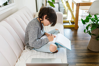 Child sitting on sofa drawing on a sketch book by open laptop - p1166m2224160 by Cavan Images