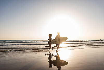 Young couple running on beach, carrying surfboard - p300m2043073 by Uwe Umstätter