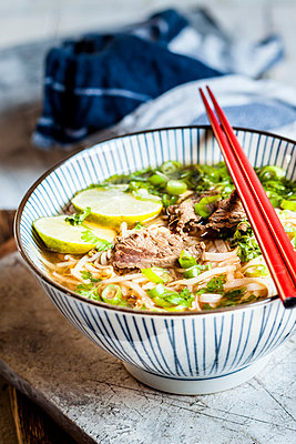 Bowl of Vietnamese Pho with rice noodles, mung beans, cilantro, spring onions and limes - p300m2104387 by Susan Brooks-Dammann
