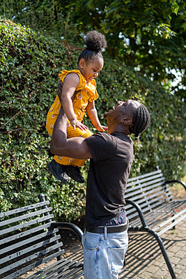 Father lifting up daughter at a bench in a park - p300m2154822 by Francesco Buttitta