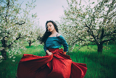 Caucasian woman dancing near flowering trees - p555m1491490 by Kateryna Soroka