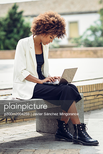 Fashionable young woman with curly hair sitting on bench using laptop - p300m2004259 von Javier Sánchez Mingorance