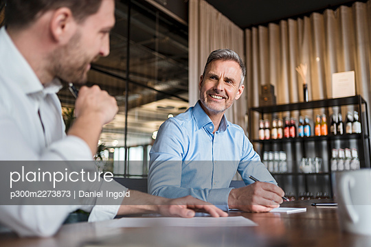 Smiling male professional with pen discussing with colleague at work place - p300m2273873 by Daniel Ingold