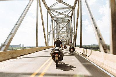 Rear view of bikers riding motorcycles on bridge against sky - p1166m1521757 by Cavan Images