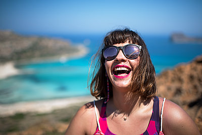 Laughing woman with turquoise lagoon in the background - p1580m2191504 by Andrea Christofi