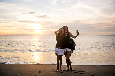 Indonesia, Bali, two women taking a selfie on the beach at sunset - p300m1356295 by Konstantin Trubavin