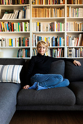 Portrait of mature woman relaxing on couch at home - p300m2144937 by Valentina Barreto