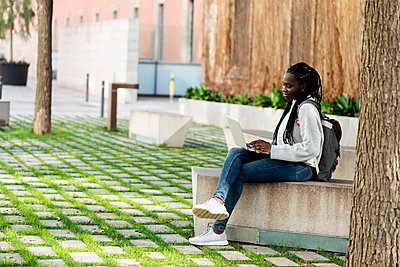 Female student using laptop on a bench - p300m2167565 by Valentina Barreto