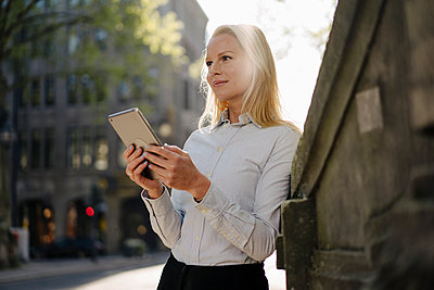 Thoughtful blond businesswoman looking away while holding digital tablet and leaning on surrounding wall in city - p300m2214010 by Joseffson
