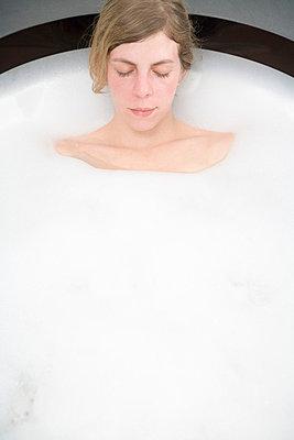 Woman lying in bubble bath - p3013857f by Stella