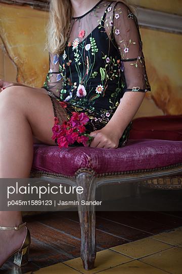 Mit Blumen auf Hocker sitzen - p045m1589123 von Jasmin Sander