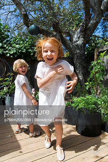 Zwei fröhliche Schwestern auf einer Terrasse - p756m2053359 von Bénédicte Lassalle