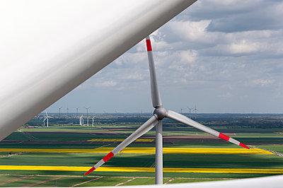 Windkraftanlage vor Rapsfeldern - p1079m1072943 von Ulrich Mertens
