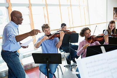 High school teacher leading music class - p1192m1085918f by Hero Images