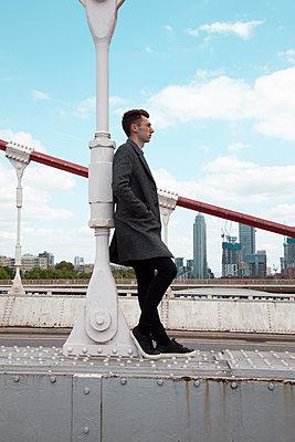 Man leaning against bridge pillar - p1248m2209176 by miguel sobreira