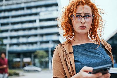 Young woman walking in the city, using smartphone - p300m2030543 von Zeljko Dangubic