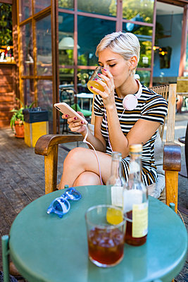 Young woman at pavement cafe enjoying soft drink while looking at smartphone - p300m2042782 by Giorgio Magini