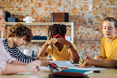 Young people sitting together at table and taking notes - p300m2144688 by Sofie Delauw