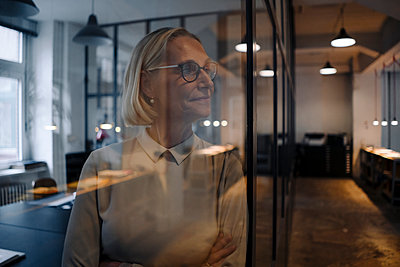 Mature behind glass pane businesswoman in office - p300m2155239 by Gustafsson