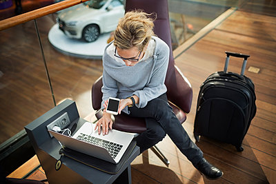 High angle view of businesswoman using laptop and smart phone at airport lobby - p426m1114695f by Maskot