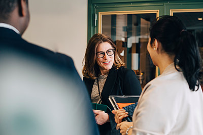 Smiling businesswoman discussing with colleagues at office - p426m1588621 by Maskot