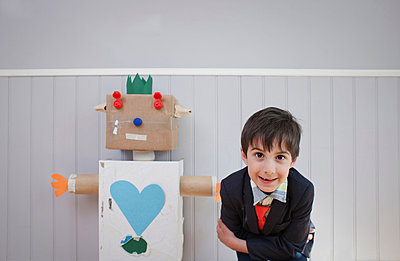 Boy leaning towards camera with homemade toy robot - p429m803094f by Ian Nolan