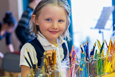 Mixed race girl smiling near multicolor pencils in classroom - p555m1410226 by Marc Romanelli