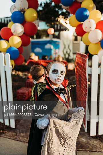 School aged boy dressed as Dracula Trick-or-Treating during Halloween - p1166m2208378 by Cavan Images
