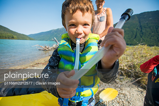 Cute boy plays with air tube for inflating boats during paddling trip - p1166m2212577 by Cavan Images