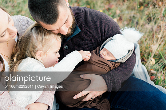 A Family of four snuggling outdoors in fall - p1166m2292811 by Cavan Images