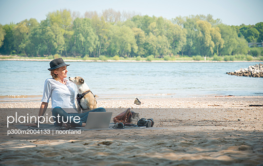 Woman sitting on blanket at a river with dog and laptop - p300m2004133 von noonland