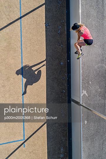 Aerial view of sportive woman jumping over barrier - p300m2005368 von Stefan Schurr