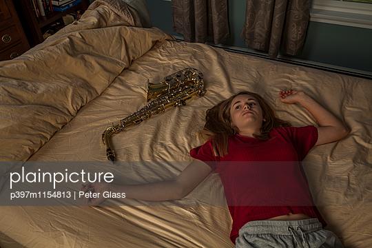 Weiblicher Teenager mit Saxophon liegt auf einem Bett  - p397m1154813 von Peter Glass