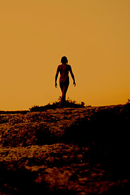 Young woman walking on a limestone beach, Provence, France - p1028m2054435 von Jean Marmeisse