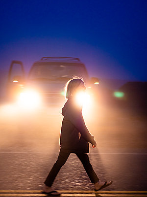 Full body profile shot of tween walking on roadway in front of lights - p1166m2153421 by Cavan Images