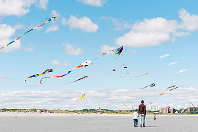 A family walking on a beach under many colorful kites - p1166m2212940 by Cavan Images