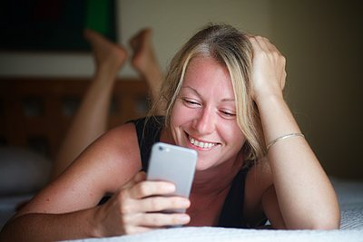 Young woman reading text message on mobile phone  - p1405m2185304 by jacquelinemccullough