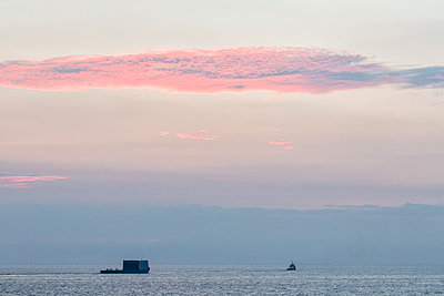 Tug towing barge from Kawaihae Harbor at sunset; Island of Hawaii, Hawaii, United States of America - p442m1179851 by Alvis Upitis